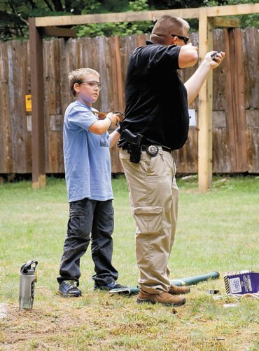 A state Environmental Conservation officer gives firearm and hunting safety training to a camper at DEC's Camp Colby in Saranac Lake last summer. (Enterprise photo — Justin A. Levine)