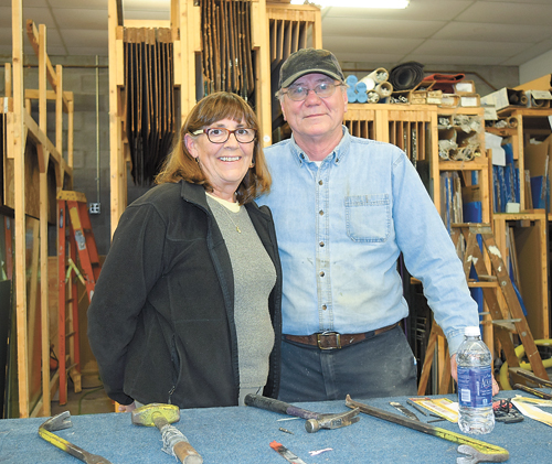 Wayne Newman, right, and his wife Lynn stand in the warehouse of Newman & Holmes on Church Street on Saranac Lake, which will close next week after more than 80 years of doing business locally. (Enterprise photo — Chris Knight)