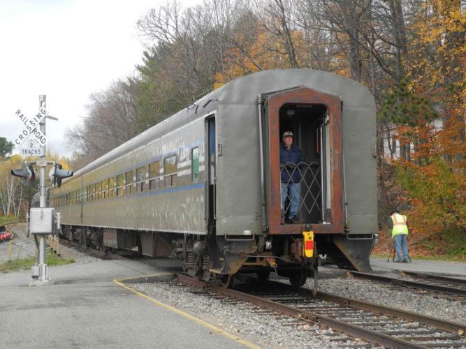 An Adirondack Scenic Railroad worker looks out of the back of the train as it leaves Saranac Lake's Union Depot on Oct. 26, 2016, after its last ride of the season — and perhaps ever. (Enterprise photo — Chris Knight)