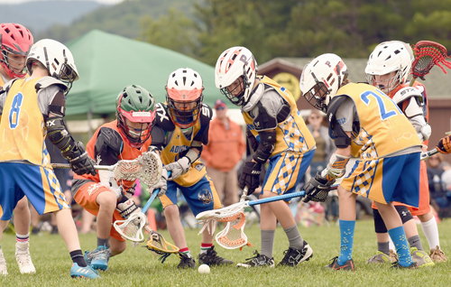 Youngsters from Orange Crush and the Adirondack Northmen battle for a ground ball during action Wednesday. (Enterprise photo — Lou Reuter)