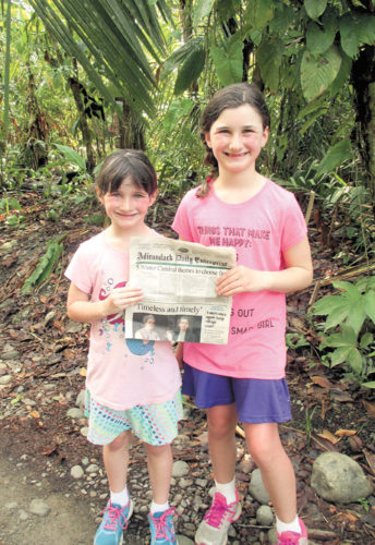 Abigail and Julia Walkow show off their hometown newspaper to the local population of white-faced capuchins in Manuel Antonio National Park, Costa Rica.