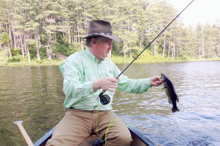 Joe Hackett hoists a nice largemouth bass he took on a flyrod popper. (Photo provided)