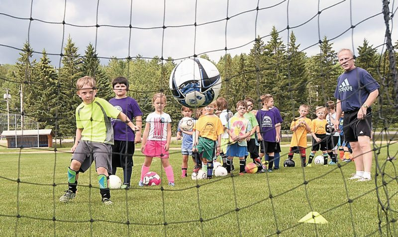 A youngster fires the ball into the net as coach Olaf Carlson and a group of might mites watch during a drill Wednesday morning at the Jim Kordziel athletic fields in Lake Placid. (Enterprise photo — Lou Reuter)