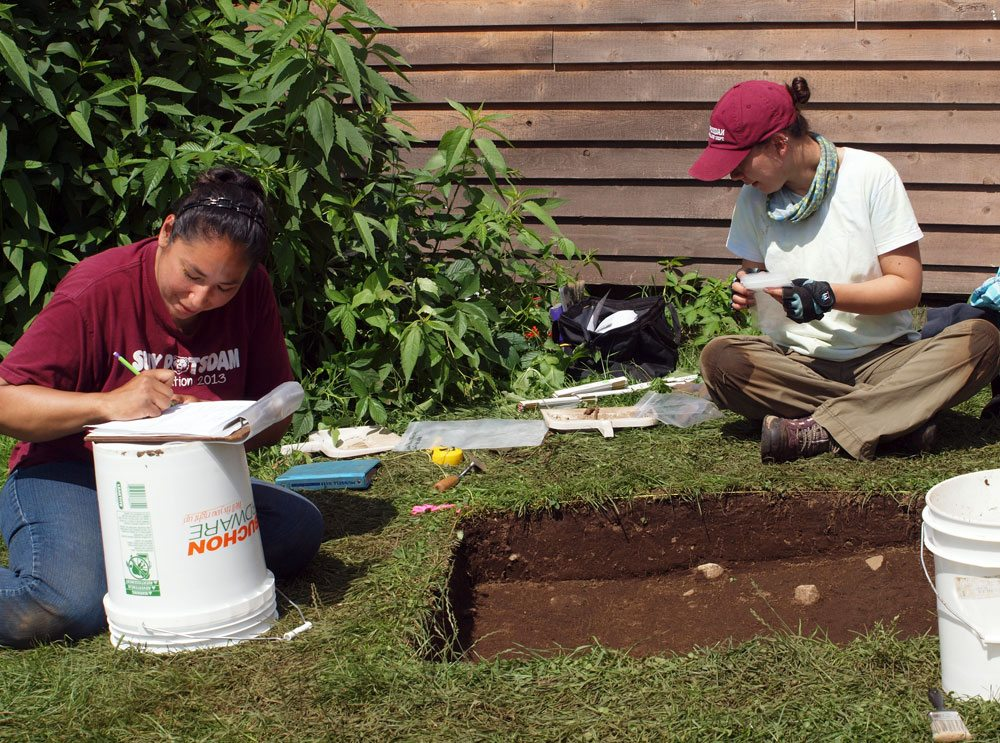 SUNY Potsdam archaeology students Marla Jacobs and Lissa Herzing record and analyze artifacts they dug up in front of John and Mary Brown's home in Lake Placid Tuesday. (Enterprise photo — Dana Hatton)