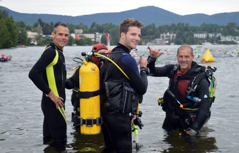 Matt Bogert (right) the captain of the Ironman Lake Placid volunteer scuba rescue team, takes a short break with several members of his crew during the middle of the 140.6-mile swim, bike, run event's swim portion. (Enterprise photo — Antonio Olivero)