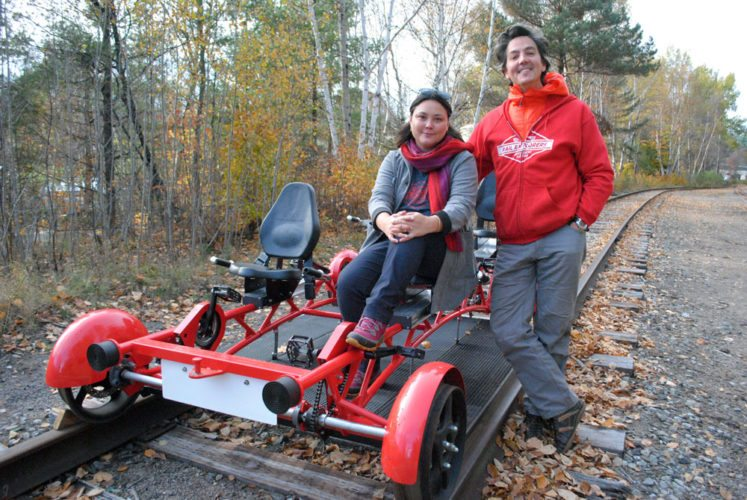 Rail Explorers owners Mary Joy Lu and Alex Catchpoole pose with one of their rail bikes in October 2015 in Saranac Lake. (Enterprise photo — Matthew Turner)