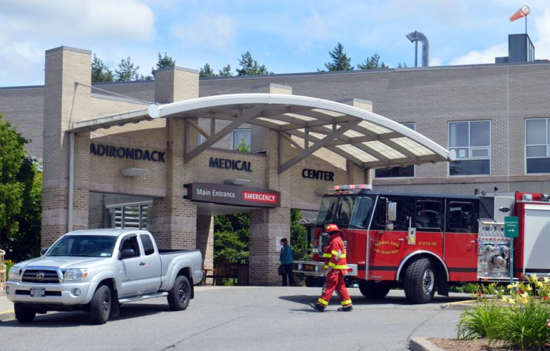 Fire driver Charlie Duprey stands beside a truck as the Saranac Lake Volunteer Fire Department responds to smoke coming from an overheating air conditioning unit inside Adirondack Medical Center early Wednesday afternoon. (Enterprise photo — Antonio Olivero)