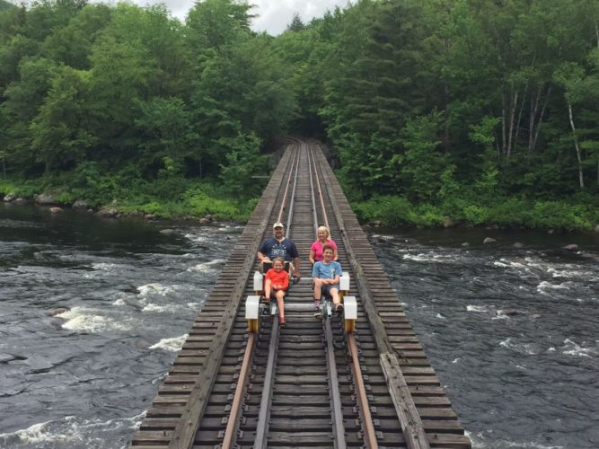 Riders take a rail bike across the Hudson River with Revolution Rail Co. on the Saratoga & North Creek Railway line in North Creek. (Photo provided by Revolution Rail Co.)