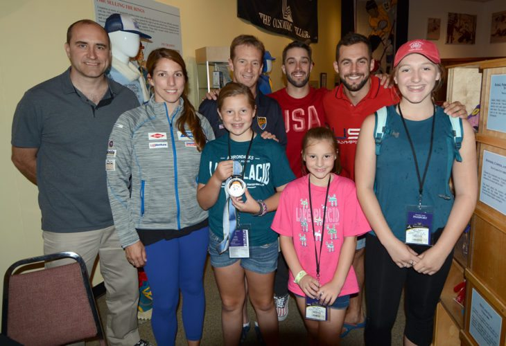 Members of the Lawless family, from the left, Cassie, Ellie and Bethany pose with members of USA Luge who were on hand to greet visitors Thursday afternoon at the Olympic Museum. Athletes, from the left, are coach and two-time Olympic medalist Mark Grimmette, Erin Hamlin, 1998 Olympic medalist Gordy Sheer, Jayson Terdiman and Chris Mazdzer. The Lawless family was in Lake Placid on vacation from their home in Peoria, Illinois. (Enterprise photo — Lou Reuter)