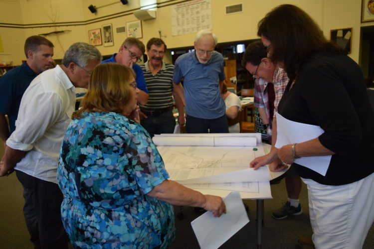 Saranac Lake school board members, with D.J. Fowler and Peg Cantwell of Franklin County Public Health in front, look over maps that identify areas in Franklin County with high lead contamination levels. (Enterprise photo — Chris Knight)