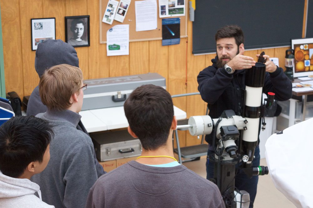Tupper Lake students look on as Joshua Thomas from Clarkson University demonstrates how to use a telescope at the Adirondack Public Observatory's offices in Tupper Lake. The observatory plans to build an Astro-Science Center to better educate students about the stars. (Photo provided)