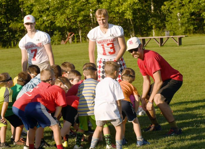 Modified coach Kyle Mochol shows flag-football age participants proper stance during Tuesday's football camp at the Saranac Lake High School football practice field. (Enterprise photo — Lou Reuter)