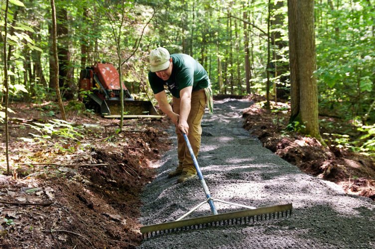 Kevin Simpson of Tahawus Trails LLC rakes the new accessible trail at The Nature Conservancy's Boquet River Nature Preserve in Willsboro. (Photo provided by The Nature Conservancy)