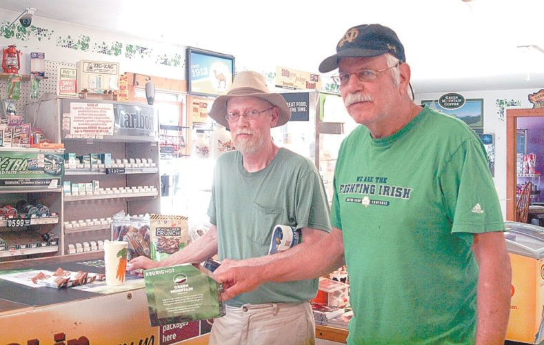 Ralph Etienne, left, and Mike Kelly, locals who have shopped at the Bloomin' Market since it opened, pose at the counter with their groceries. (Enterprise photo — Dana Hatton)