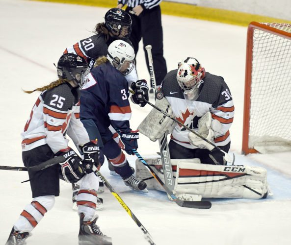Sydney Shearen of the U.S. mixes it up while attempting to control an airborne puck in front the net guarded by Canadian goaltender Madelyn McArthur during the third period of Thursday's game. (Enterprise photo — Lou Reuter)
