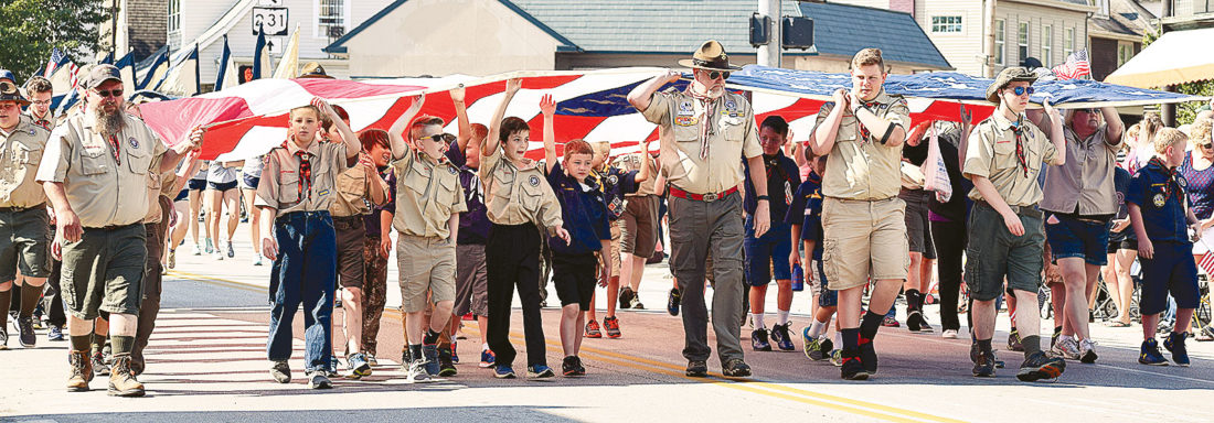 PHOTO BY JILL GOSCHE Boy Scouts carry an American flag down Washington Street during Tiffin's Memorial Day parade Monday morning.