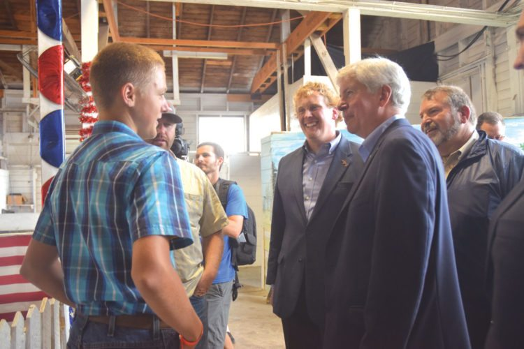 Haley Gustafson   Daily Press  At left, Jace Moker, whose steer was named grand champion at the Beef Cattle Junior Show, is congratulated by Gov. Rick Synder, right, while Ed McBroom, a former state representative, middle, looks on Thursday afternoon during the governor's visit to the Upper Peninsula State Fair in Escanaba.