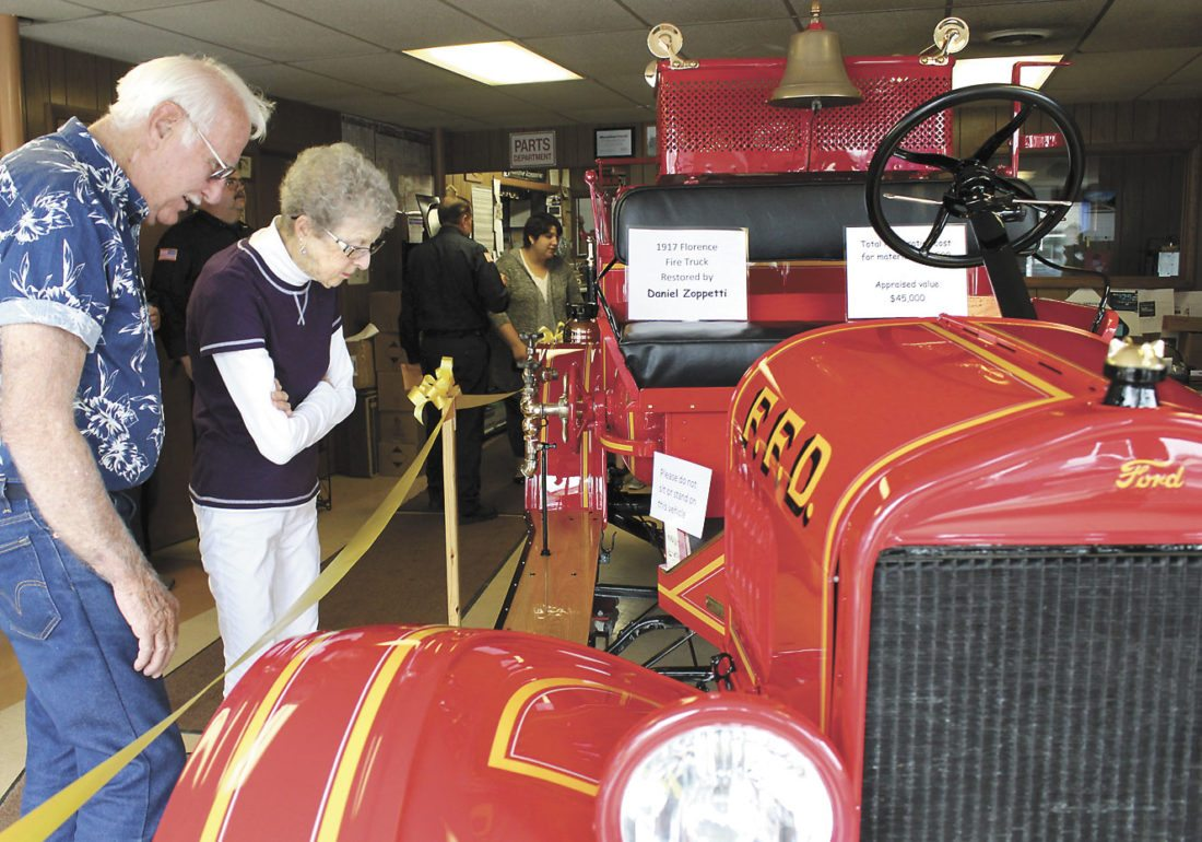 FROM LEFT, CAROL and Chet Tokoly from Homestead attended the unveiling last month of the restored the 1918 Florence fire truck will be featured at the U.P. Firemen Tournament that starts Friday in Florence. The truck has been totally restored by Daniel Zoppetti, auto body expert from Luxenberg, Wis. (Theresa Proudfit/Daily News photo)