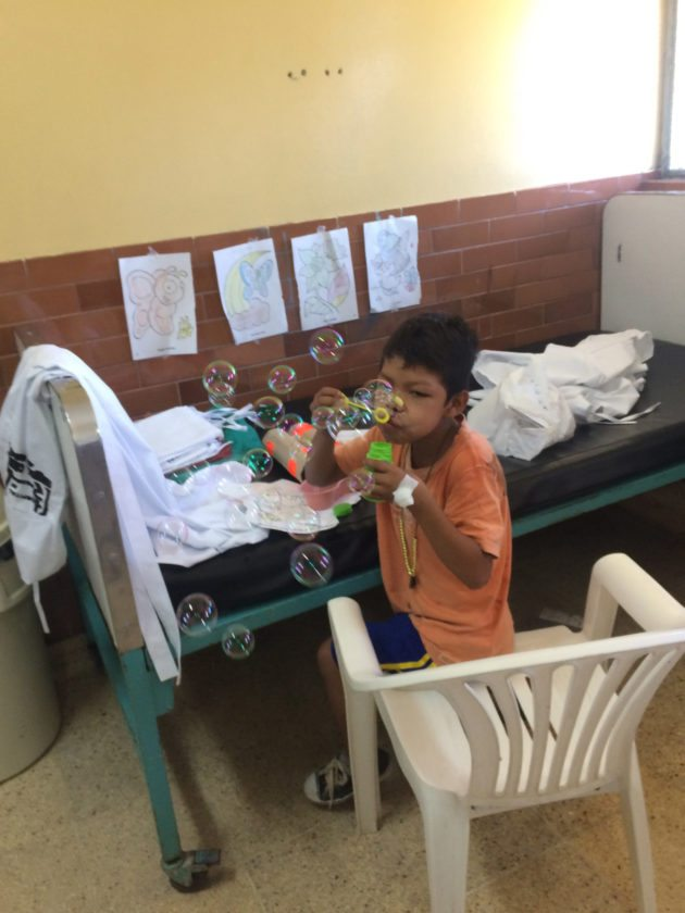 A young patient blows bubbles for the first time in his life after surgery that was provided by Dr. Casuccio and his team in Peru.