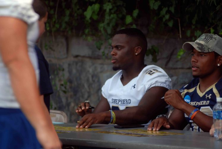 Journal photos by Eric Jones Shepherd's DeonteGlover, left, and TreAnderson sign autographs during theRams' media day on Saturday in Shepherdstown.