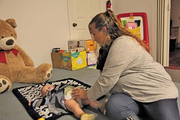 Alida Scott changes the diaper of her son, Anthony, at No Bottom Left Behind in Johnstown last October. The organization is looking for donations to keep its supply of diapers and baby products available. (The Leader-Herald/Patricia Older)