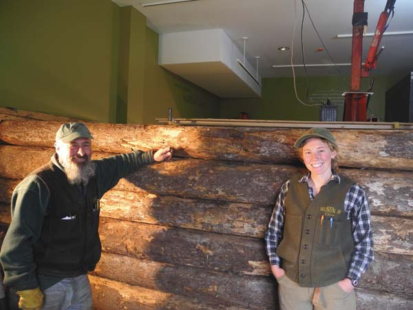 """Michael Frenette and Chloe Mattilio pose April 20 with their in-progress reassembly of """"Woodswoman,"""" author Anne LaBastille's log cabin, inside the Adirondack Experience museum in Blue Mountain Lake. They previously disassembled the cabin from its original location at Twitchell Lake, near Big Moose. (Enterprise/Ben Gocker)"""