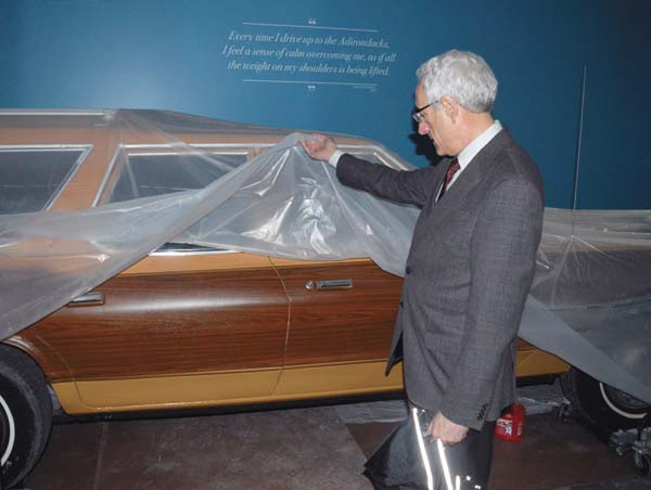 David Kahn, executive director of the Adirondack Experience, lifts a plastic cover from a station wagon that will be part of the museumÕs upcoming ÒLife in the AdirondacksÓ permanent exhibit. Part of the exhibit shows how visitors have gotten to the Adirondacks over the years. (Enterprise photo/Antonio Olivero)
