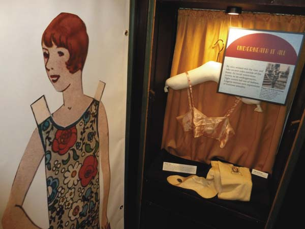 """In the bedroom area of Historic Saranac Lake's new """"Roaring Twenties"""" exhibit, a life-size image of a 1920s paper doll stands next to a display on womenÕs underwear of the decade. WomenÕs clothes of the decade reflected increased feminism and female sexuality as well as boyish figures being in vogue. (Enterprise photo Ñ Peter Crowley)"""