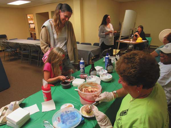Stephanie Seelow and her niece, Autumn Oare, 6, both of Gloversville, are served ice cream by Patty Franco, left, and Wanda Ellis, Friends of the Gloversville Public Library Friday during an ice cream social. (The Leader-Herald/Eric Retzlaff)