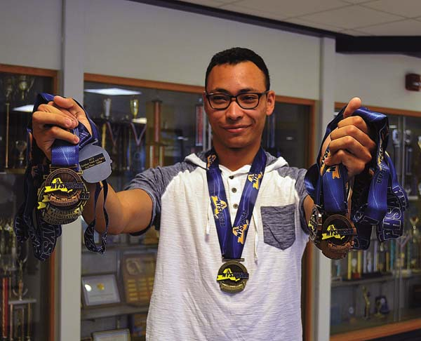 Former Amsterdam track star Izaiah Brown hold up the 11 medals presented to him by the New York State High School Athletic Association to replace the ones that were destroyed in a fire at his family home last August. (The Leader-Herald/James A. Ellis)