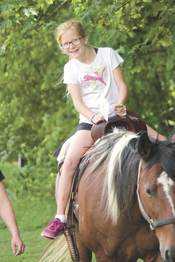 Sentinel photo by JULIANNE CAHILL Janae Swartz, fourth grade student, enjoys a ride on horseback Friday morning during field day at Fermanagh-Mifflintown Elementary School. Swartz is pictured atop 'Sir Duke,' led by Juniata Saddle Horse Association members Anita Wagner and Christie Hockenberry. The organization brought several horses to the school for the event.