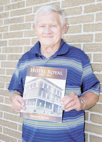 Sentinel photo by BUFFIE BOYER Wayne Taylor, of Mifflintown, displays a copy of his new softback book tracing the history of Port Royal's Hotel Royal.