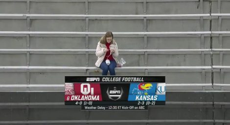 A screenshot from an ESPN broadcast shows a woman crocheting before the University of Kansas' home football game against Oklahoma, Saturday, Oct. 5, 2019.