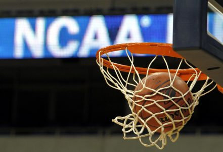 In this March 20, 2010, file photo, a ball flicks through the net in front of the NCAA logo on the marquis during an NCAA college basketball practice in Pittsburgh. (AP Photo/Keith Srakocic, File)