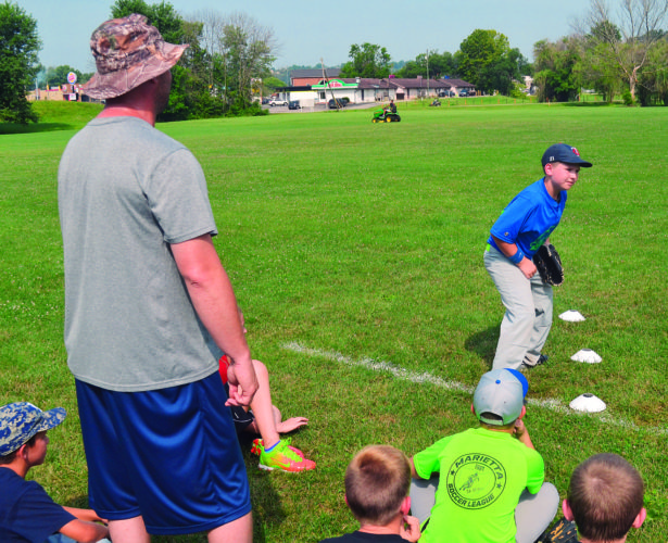 Parkersburg 10-year-old Walker Jones, right, gets instruction from teacher Matt Warden at an outfield station in the MC Camp of Champs Wednesday at Don Schaly  Stadium.  RON  JOHNSTON The Marietta Times