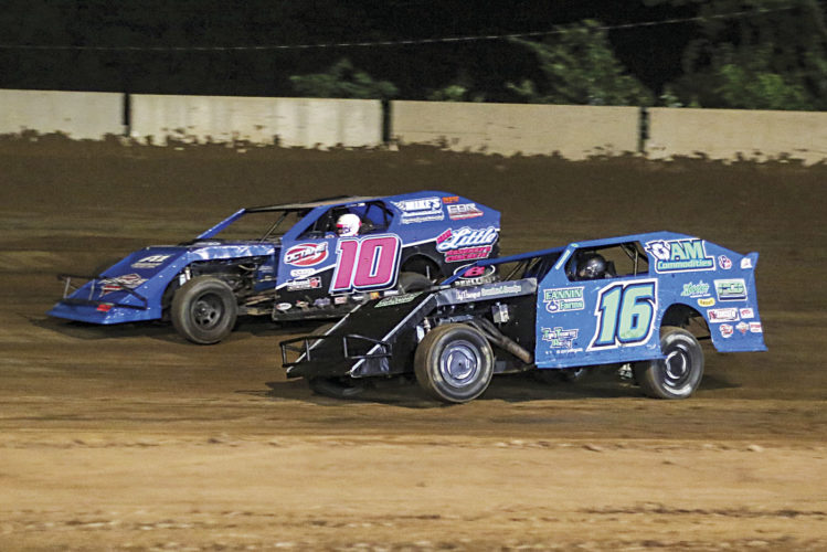 Third generation racers Travis Dickson (16) and Kyle Bond (10) battle for the lead in the 20 lap AMRA Modified feature Friday night at The Legendary Hilltop Speedway. Dickson would go on to capture his first win of the season at the track. Photo courtesy of Zach Yost.