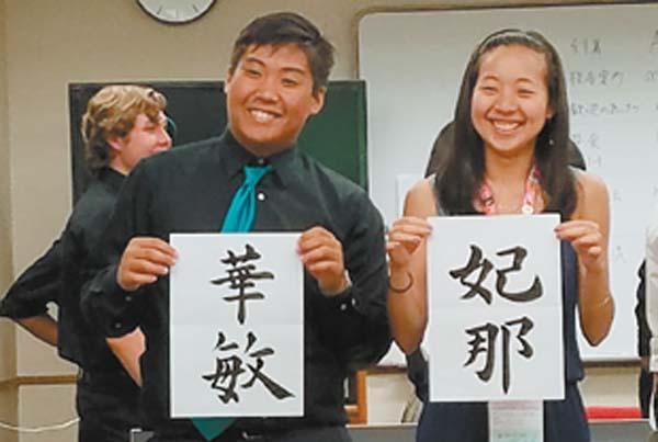King Kekaulike High School jazz band members Kevin Fukumoto and Hina Okabe display their names written in calligraphy at Daito Bunka University Dai Ichi High School in Japan.