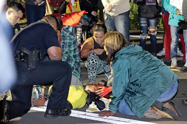 Protesters and police surround David Prais as he lies unconscious early Wednesday morning near the intersection of Haleakala Highway and Kekaulike Highway. Some protesters believe police used excessive force in restraining Prais, although police said Prais struggled with officers and refused to follow orders. The Maui News / COLLEEN UECHI photo