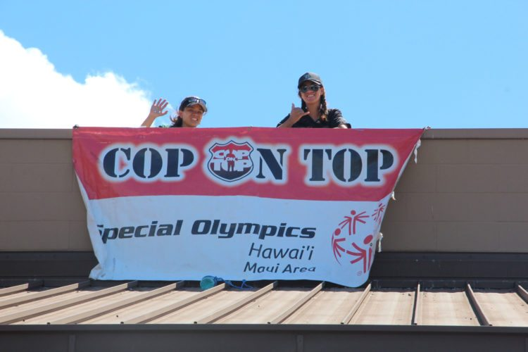 Wailuku patrol officers Colleen Loo and Bethany Cravalho-Parker wave on Thursday atop Walmart in Kahului as part of the 16th annual Cop on Top fundraiser for Special Olympics Maui.  • Maui Police Department / KAMUELA MAWAE photo