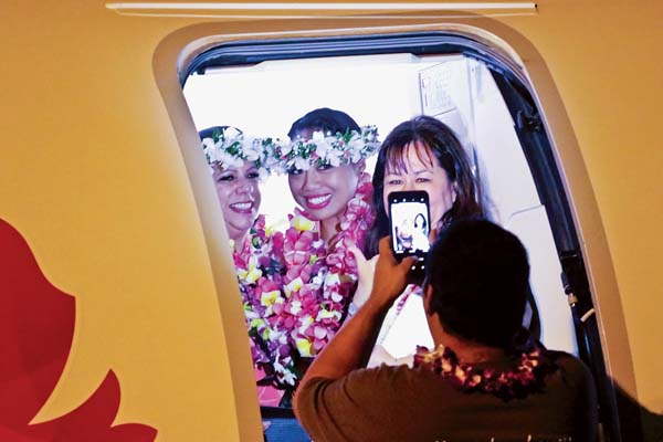 Kimi Tamanaha (right), Island Air airport operations manager on Maui, poses for a cellphone photo with flight crew members as the last Island Air flight to Honolulu completed boarding Friday night at Kahului Airport. -- BEN JUAN photo