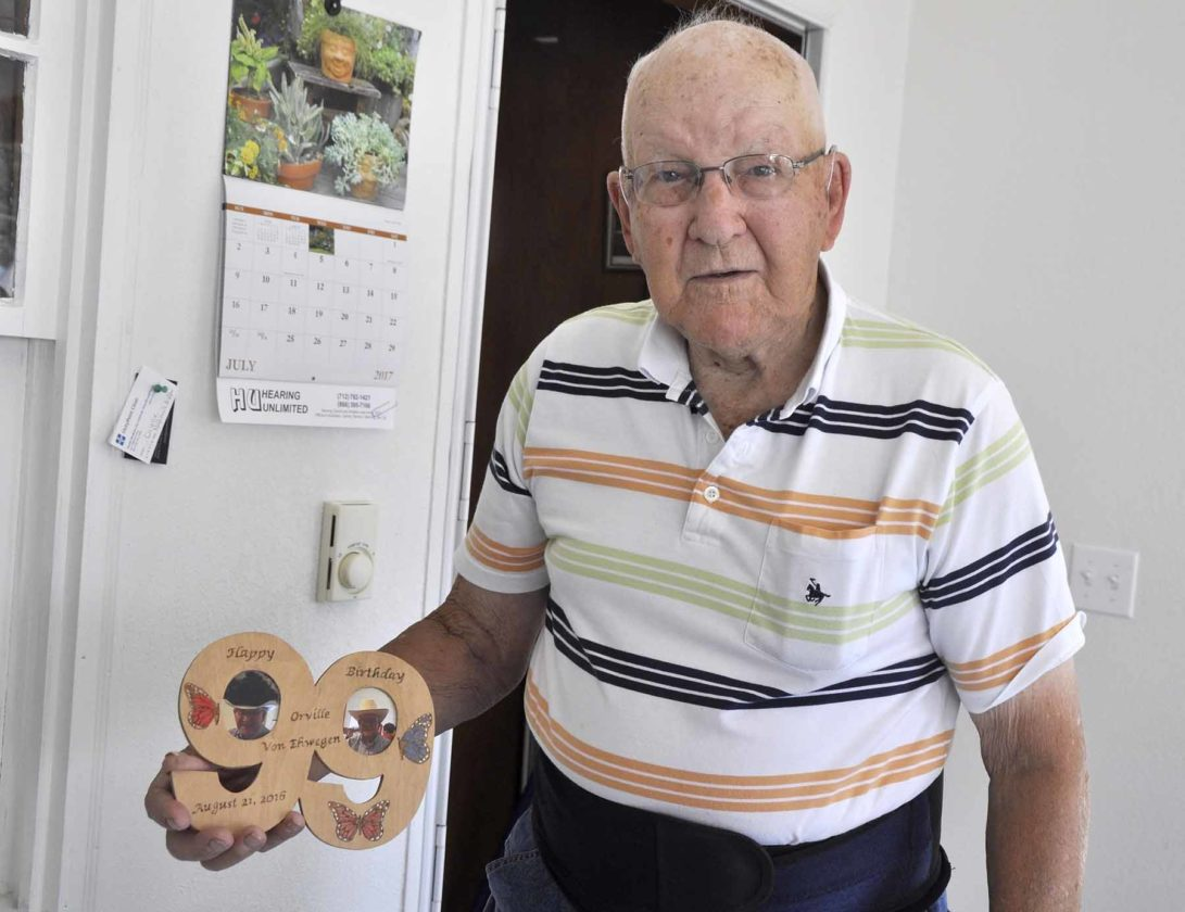 "-Messenger photo by Peter Kaspari  Orville Ehwegen shows a carved number ""99"" that was given to him for his 99th birthday last year. Ehwegen, of Sac City, will turn 100 years old on Aug. 21."