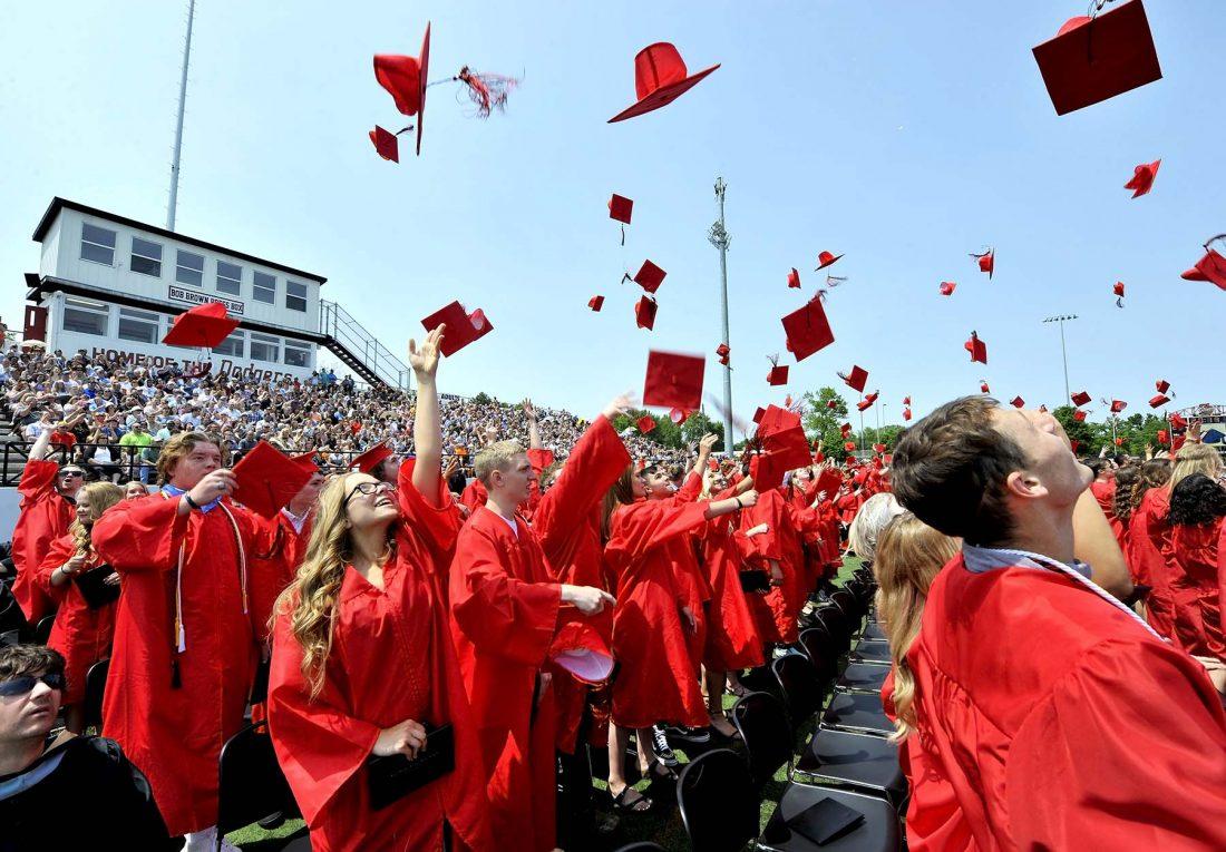 Graduates through caps in air outside