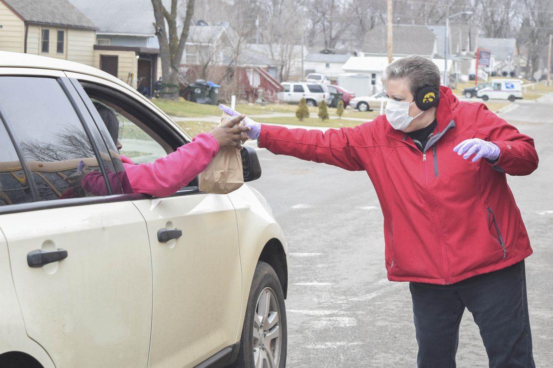 women passing bag into car through window