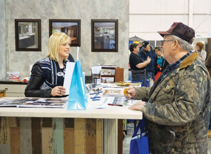 Jill Schramm/MDN  Erika Kelly, interior designer with Souris River Designs, visits with a visitor to the Home and Garden Show in Minot March 4. Builders and home companies were at the show to show what's available for 2017.