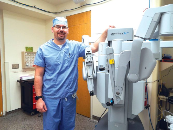 Submitted Photo  Dr. David Amsbury stands next to the da Vinci robot surgical machine.