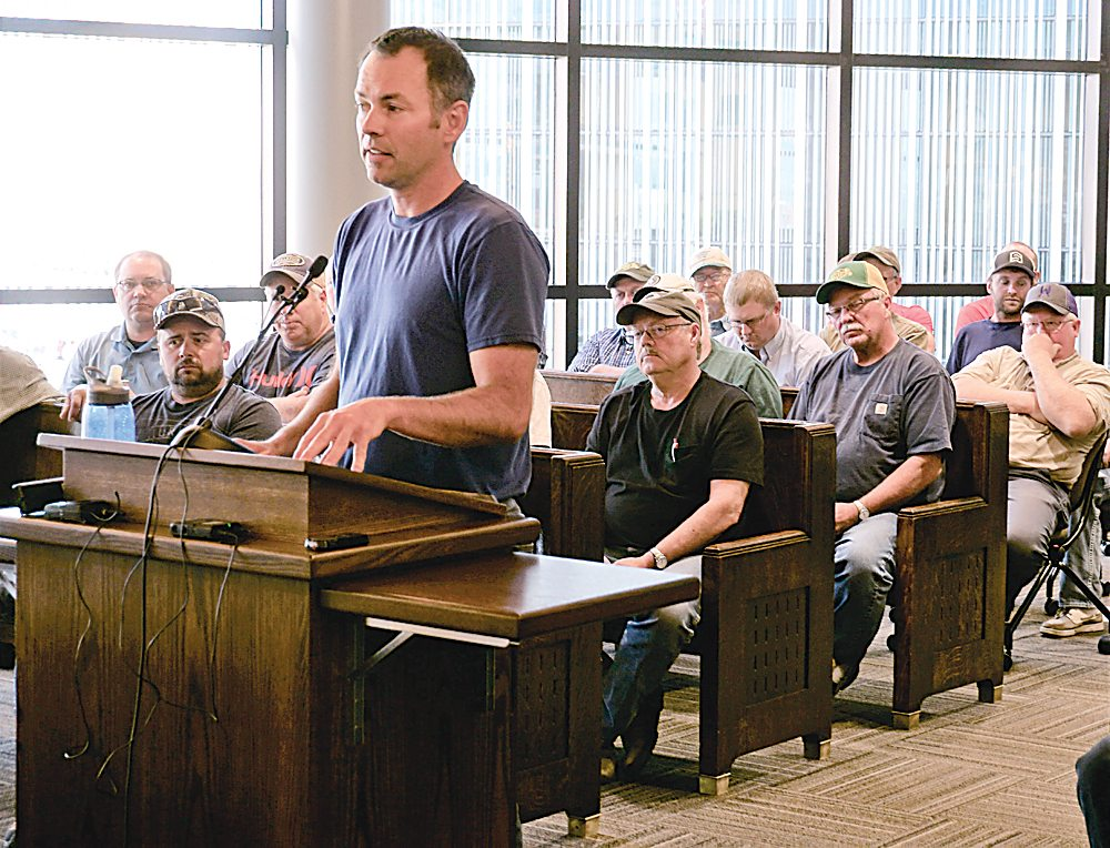 Roger Neshem  addresses the Ward County Commission Tuesday, backed  by area farmers.  Jill Schramm/MDN