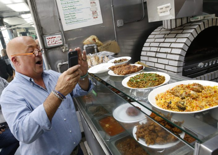 """In this Thursday, July 20, 2017 photo, the Travel Channel's """"Bizarre Foods"""" host Andrew Zimmern snaps a cell phone photo of chicken kebabs, far left, a dish composed of organ meats, center, and a goat dish called katakat at Kababish, a Pakistani, Indian and Bangladeshi takeout food shop in the Jackson Heights section of New York. Zimmern says, """"I purposely set out to make a show that's entertaining,"""" he said. """"At the same time I try to be very thoughtful and thought-provoking and I try to educate and I take the cultural lessons of the show very, very, very seriously."""" A new show, """"The Zimmern List,"""" debuts early 2018 showcasing his favorite places, """"where I actually go when the cameras aren't rolling."""" (AP Photo/Kathy Willens)"""