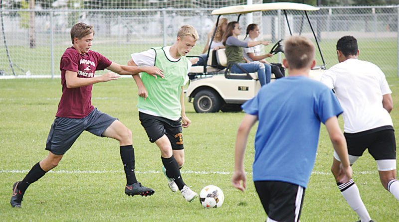 Alex Eisen/MDN Senior Isaac Kauffman (green) fends off junior Cody Burke (maroon) during a Minot High boys' soccer practice Monday at the Optimist Soccer Complex.