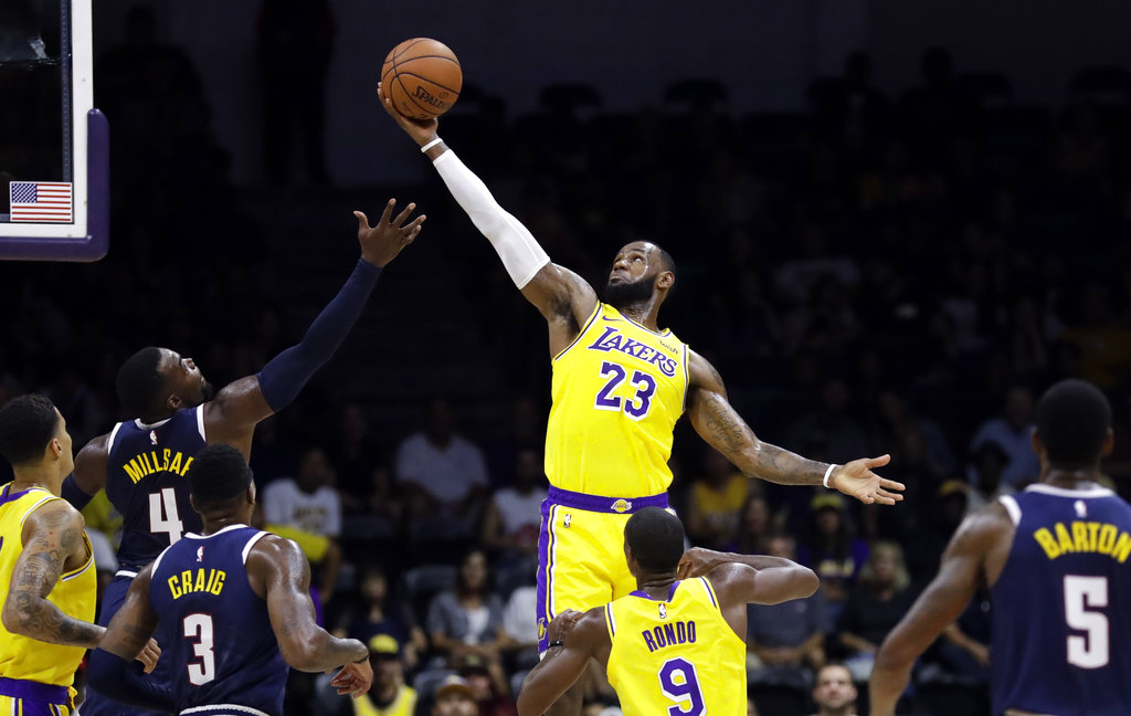 5e36798a96f8 Los Angeles Lakers forward LeBron James (23) grabs a rebound over Denver  Nuggets forward Paul Millsap (4) during the first half of an NBA preseason  ...