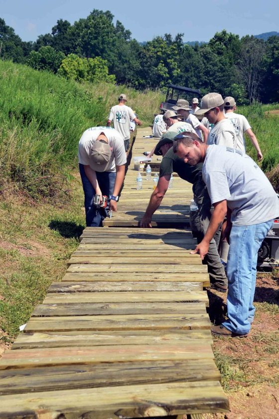 Scouts from Grand Canyon Council's Troop 3324 and personnel at Mountwood Park in Wood County work to construct a 100-foot raised wooden boardwalk as part of the park's trail system. The troop is on its way to the National Boy Scout Jamboree at Summit Bechtel Family National Scout Reserve near Beckley, W.Va. They stayed at Mountwood Monday and Tuesday nights and did the service project as part of their commitment to Scouting principles. (Photo by Brett Dunlap)